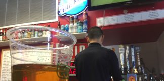 clear cup with beer inside a man with a black shirt with his back turned to the camera