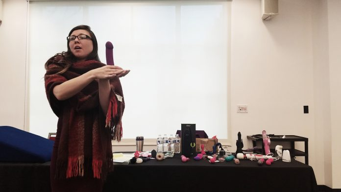 woman wrapped in scarf holds purple dildo in palm while speaking to an audience