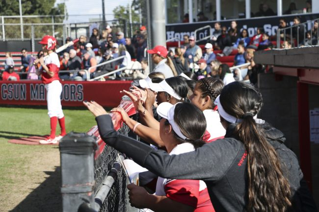 CSUN softball players excitedly stand in the dugout