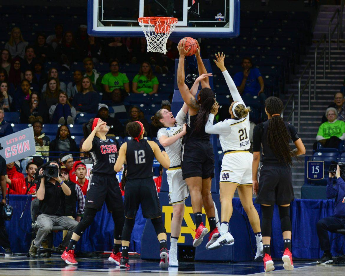 CSUN womans basket ball player dressed in black surrounded by opponents jumps to take a shot