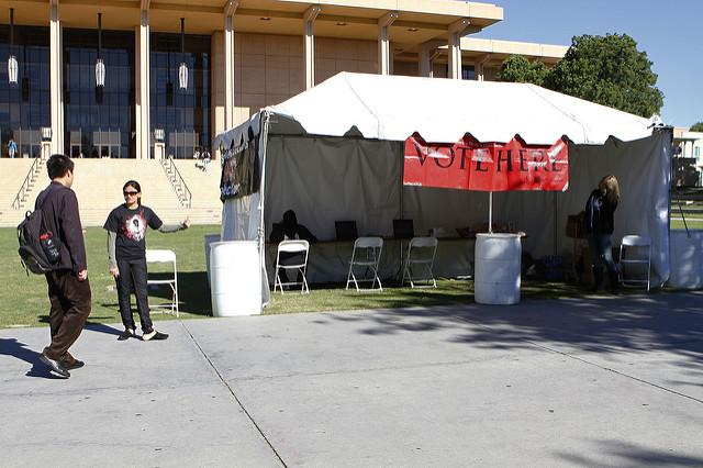 A member of the AS Election's street team encourages a fellow student to vote, with voting stations provided in a booth in front of the Oviatt library. Photo credit: File Photo/The Sundial