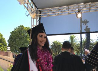 happy woman dressed in black cap and gown