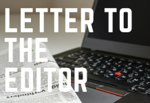 large bold white lettering in front of a black laptop and a newspaper
