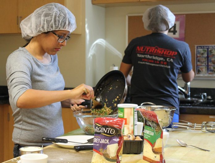 woman in grey shirt and hair net focuses while putting food in a bowl