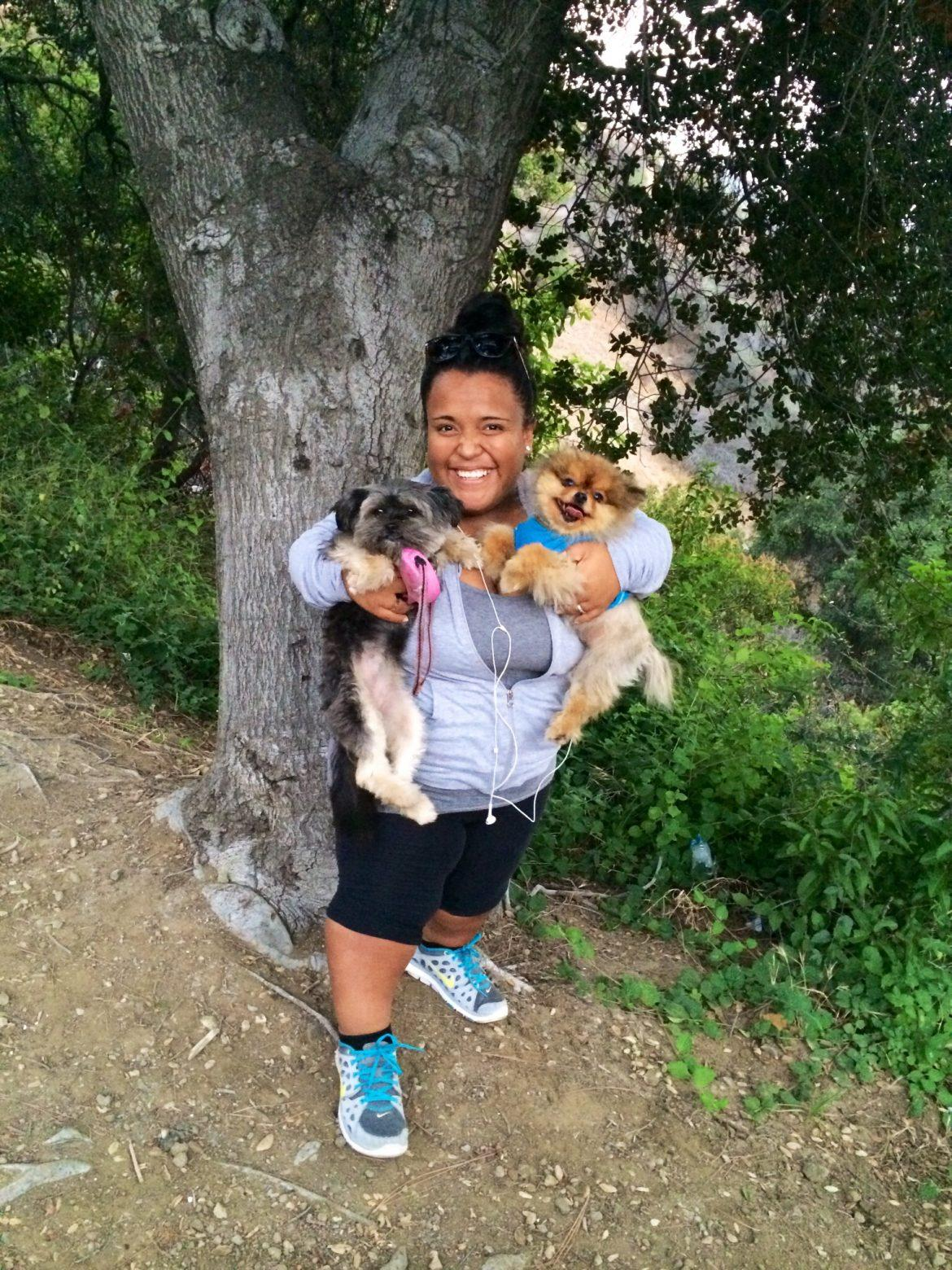 woman in workout clothes happily hold two dogs in her arms
