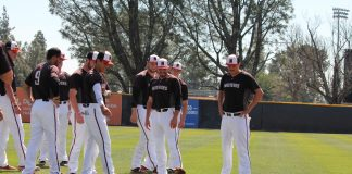 CSUN matadors baseball team on the field happily looking at a wiener dog