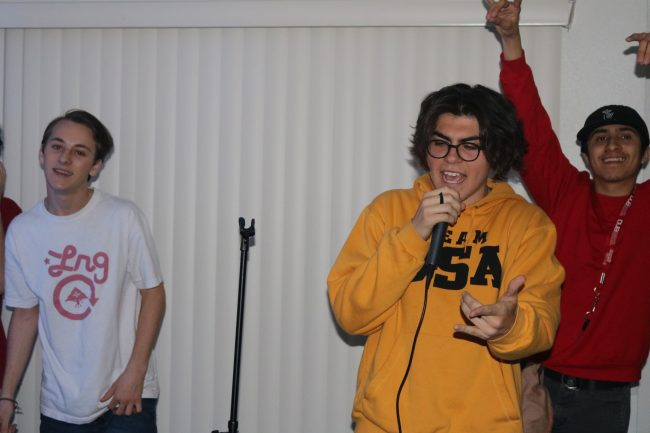 man in yellow sweater holds mic and performs passionately