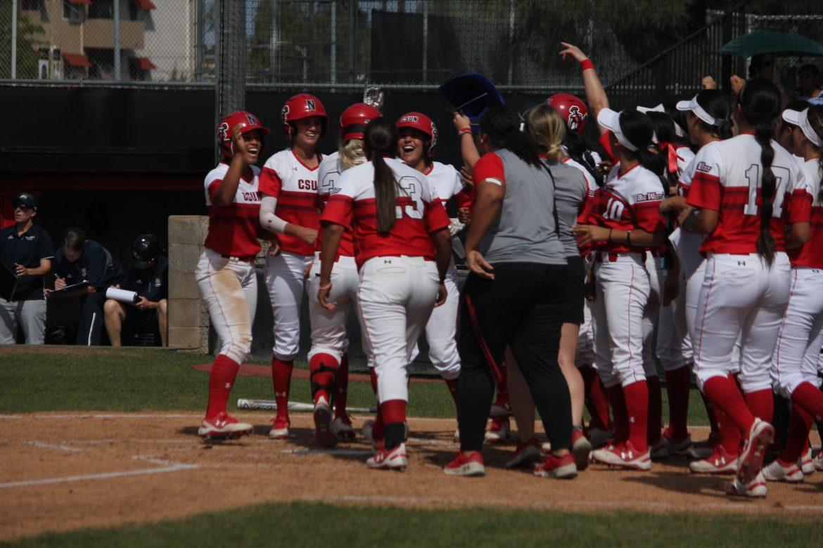 csun+softball+players+in+red+and+white+celebrating+on+home+base