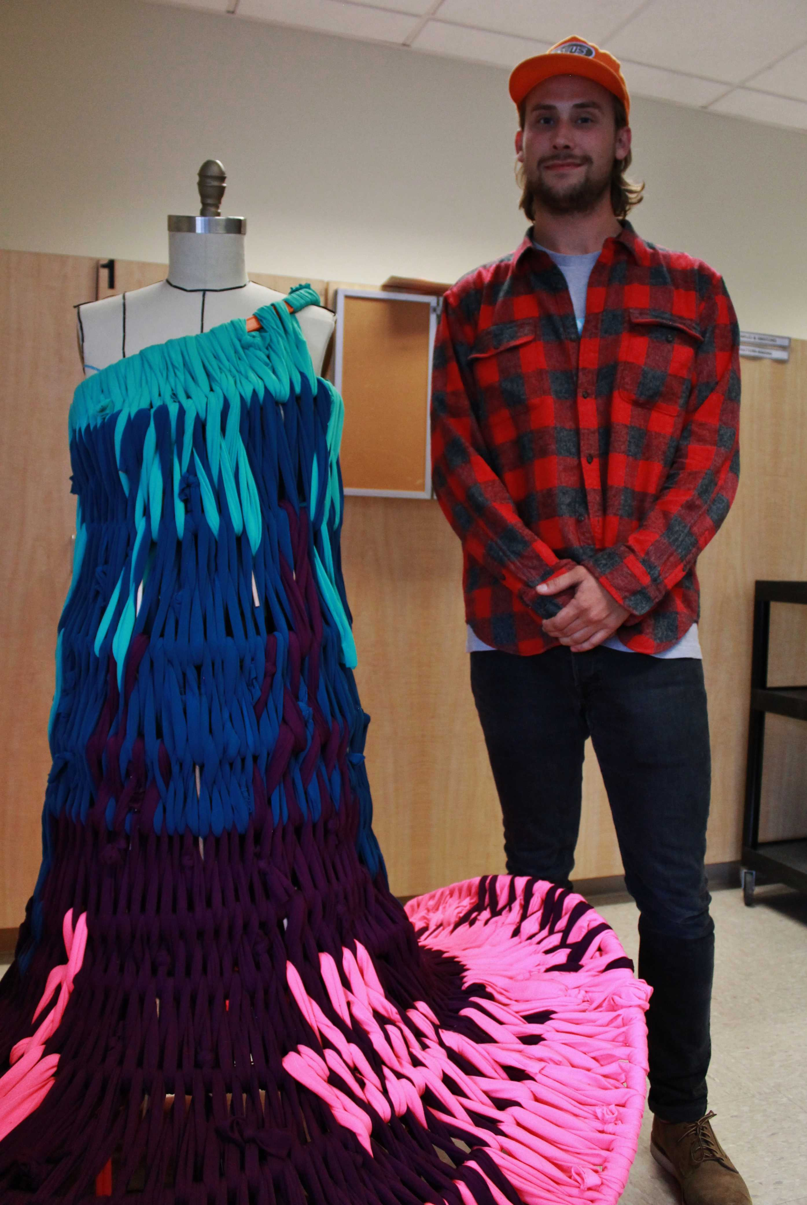 man in red plaid stands beside mannequin with colorful dress