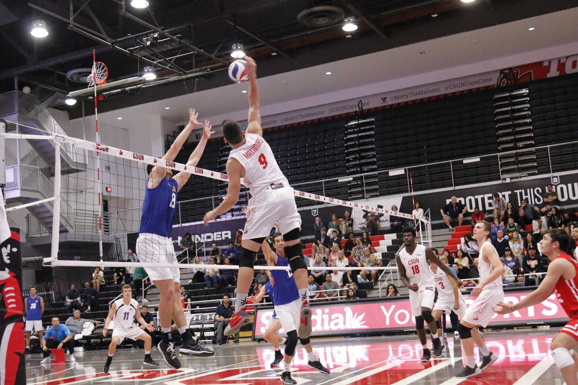 csun mens volleyball player in white goes to spike the ball