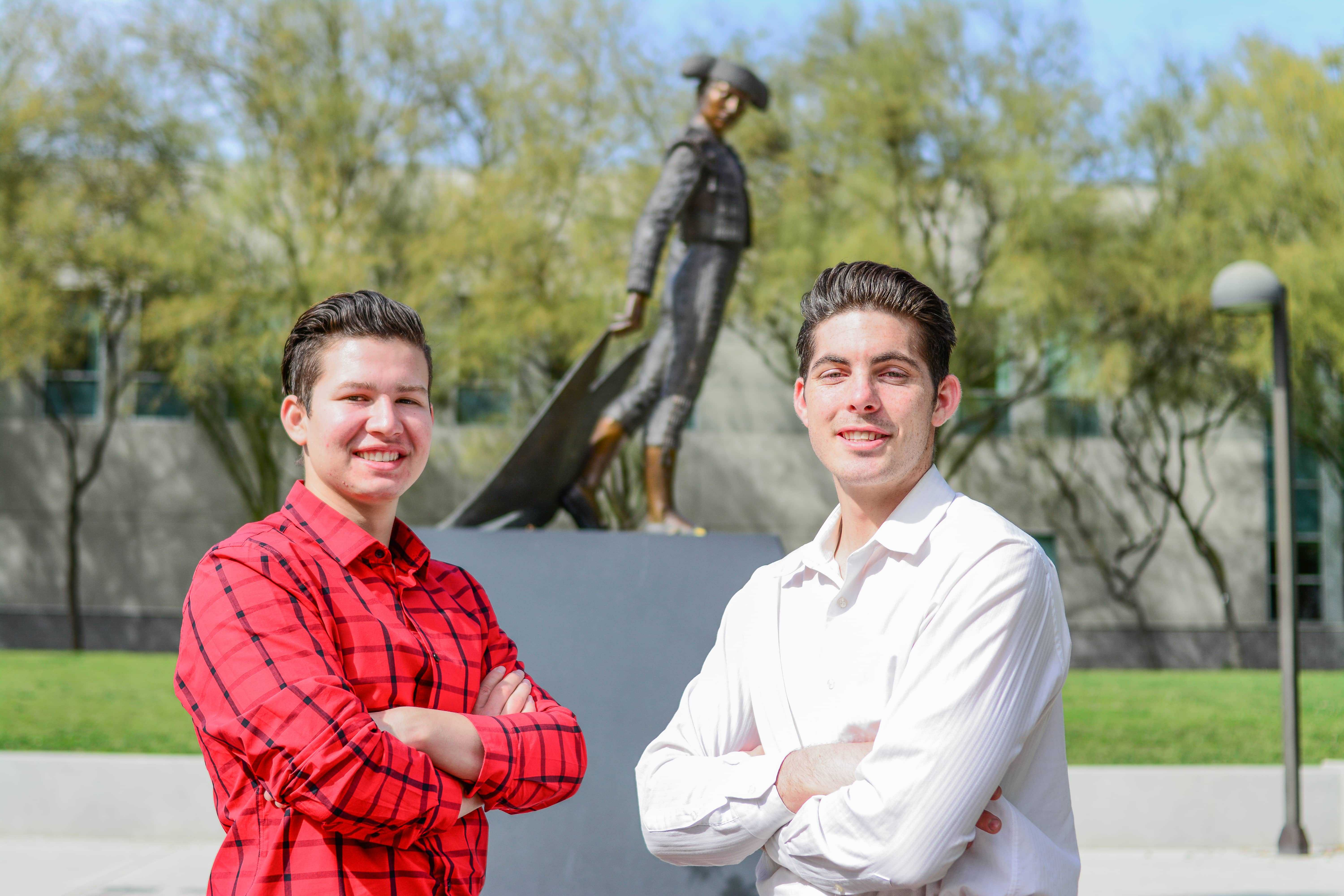 two men pose with arms crossed in front of the matador statue