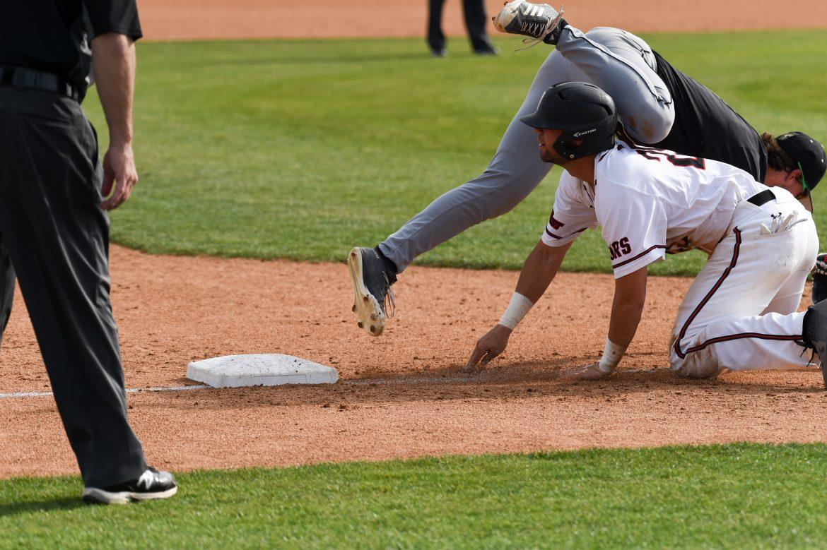 Trevor+Casanova+slides+back+to+third+base+and+crashes+into+the+Cal+Poly+third+baseman.+Photo+credit%3A+Peter+Griffin