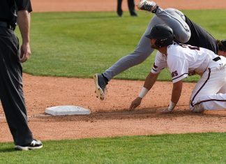 csun baseball player in white on all fours while opposing player falls over him