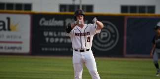 CSUN mens baseball player in white uniform stands at base while motioning at something with his hands