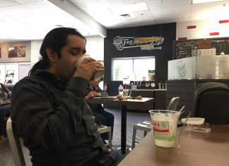 man sits at table and sips coffee