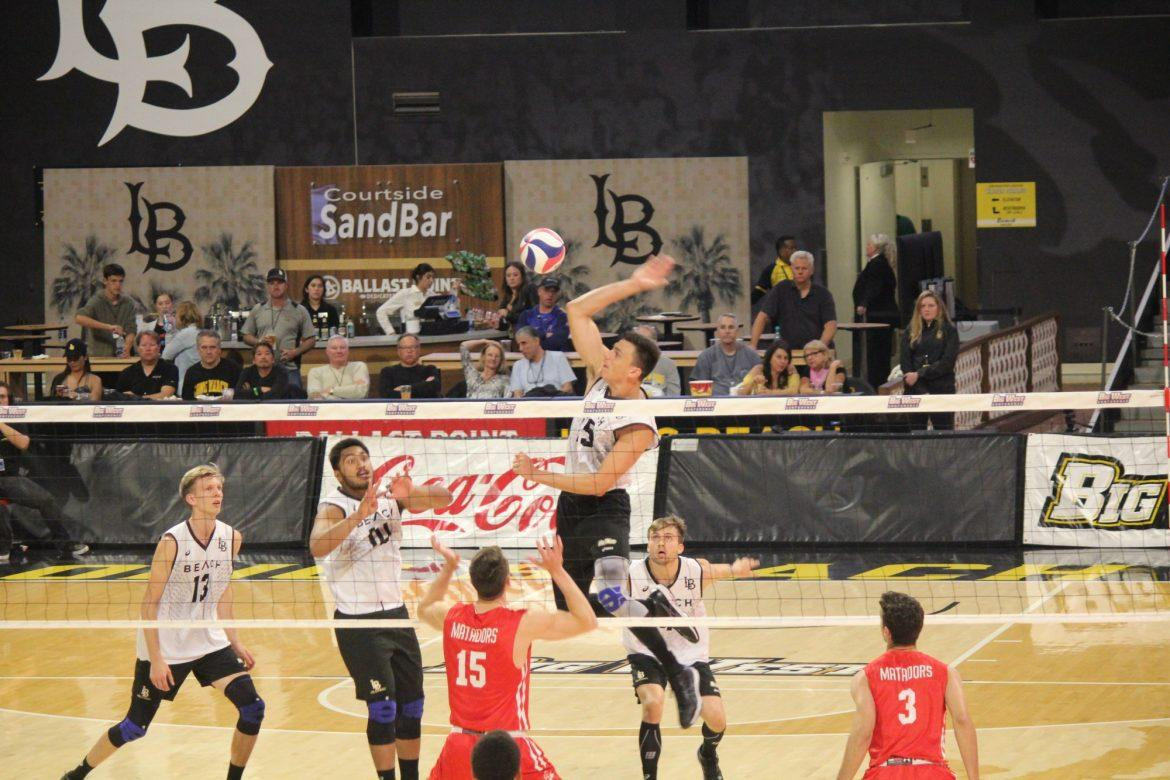 Beach%27s+middle+blocker+Nick+Amado+soars+to+a+quick+set+on+the+net+towering+over+Eric+Chance.+Photo+credit%3A+Justin+Vigil