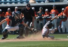 CSUN baseball player in grey uniform slides to base while opponent tries to tag him out