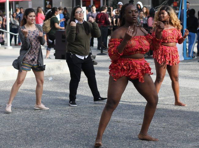 two women in red traditional wear teach other women dressed causally how to dance