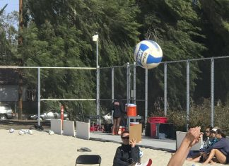 woman hits ball up into the air during sand volleyball