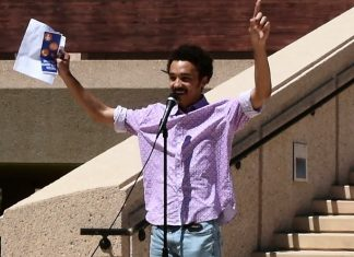 man in purple button down stands with hand in air behind microphone
