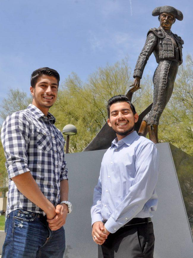 two men happily pose in front the matador statue