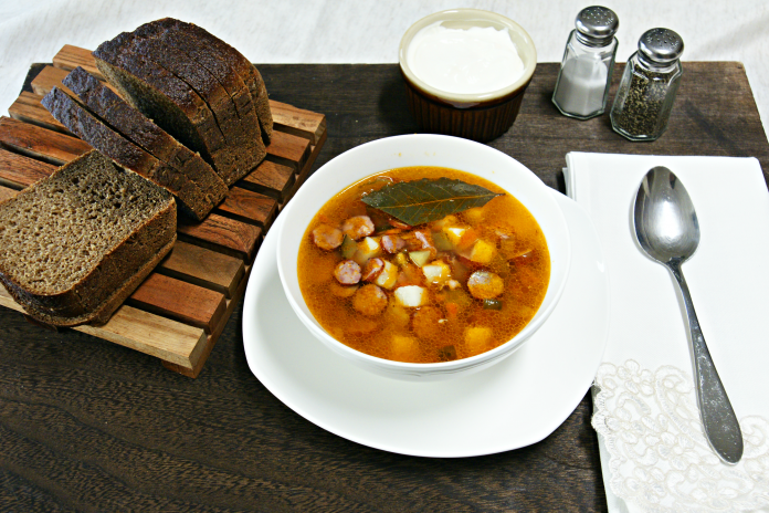 plate of orange colored soup on a white plate with toast and sour cream on the sides