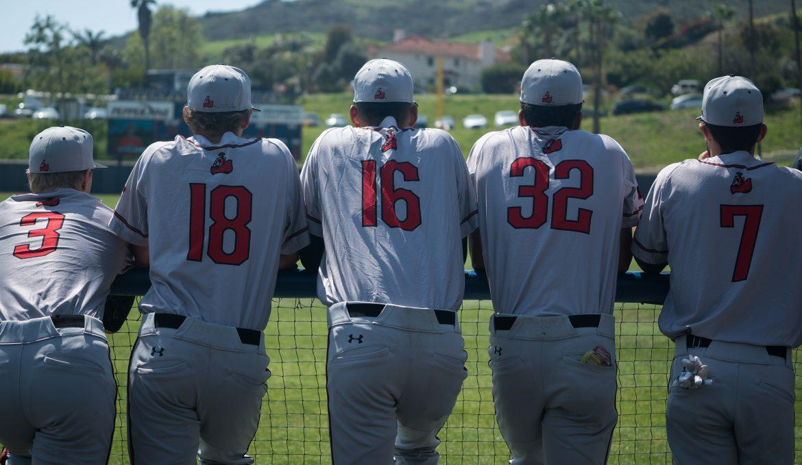 CSUN+baseball+players+in+grey+uniforms+lean+against+railing+as+they+watch+the+game