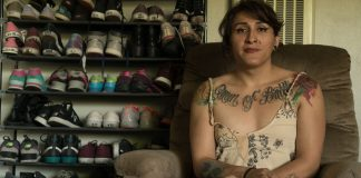 woman sits on recliner with racks of shoes behind her