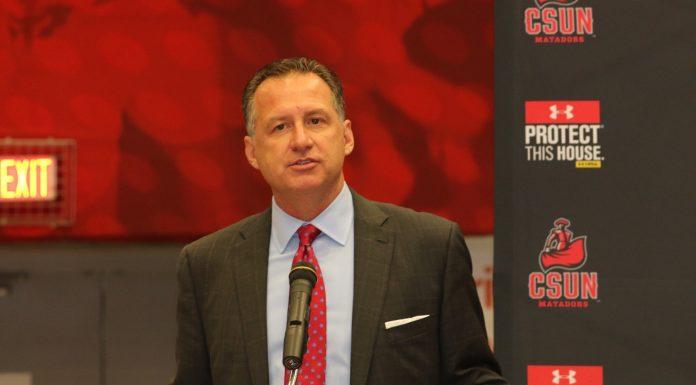 man in grey suit speaks behind podium