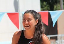 female water polo player happily holds ball as she stands next to pool