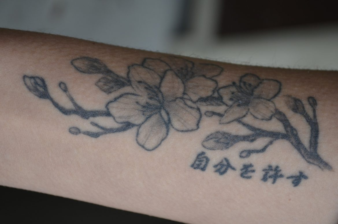 black tattoo of cherry blossoms on a persons forearm