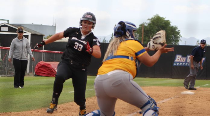 CSUN womans softball player dressed in black runs to base where opponent is waiting to catch the ball