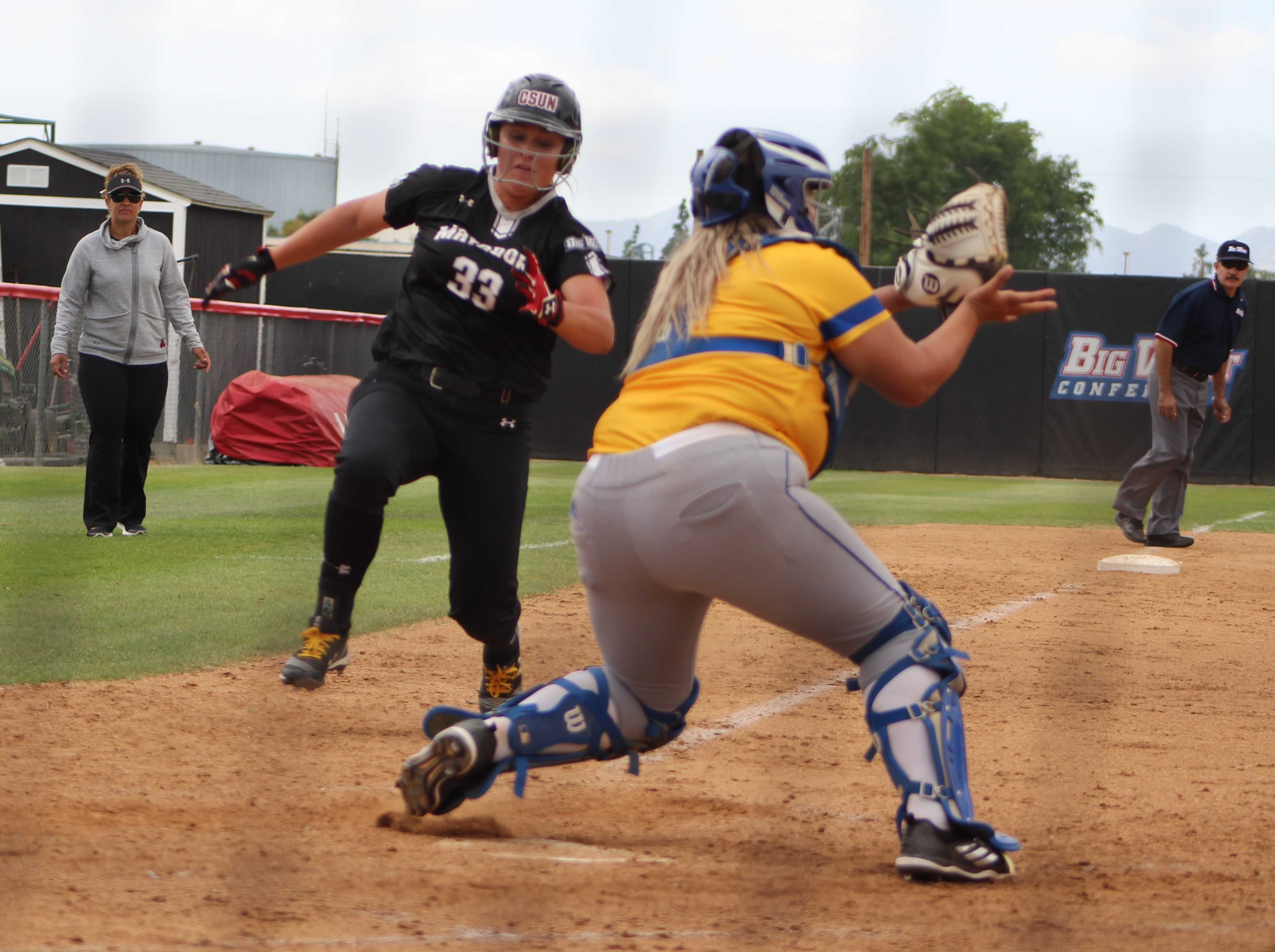 Sophomore Megan Stevens attempts to touch home base to keep the lead against UC Santa Barbara. Photo credit: Justin Lee