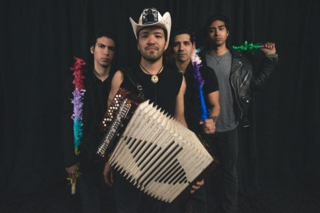 four men stand seriously with piñata sticks and an accordion