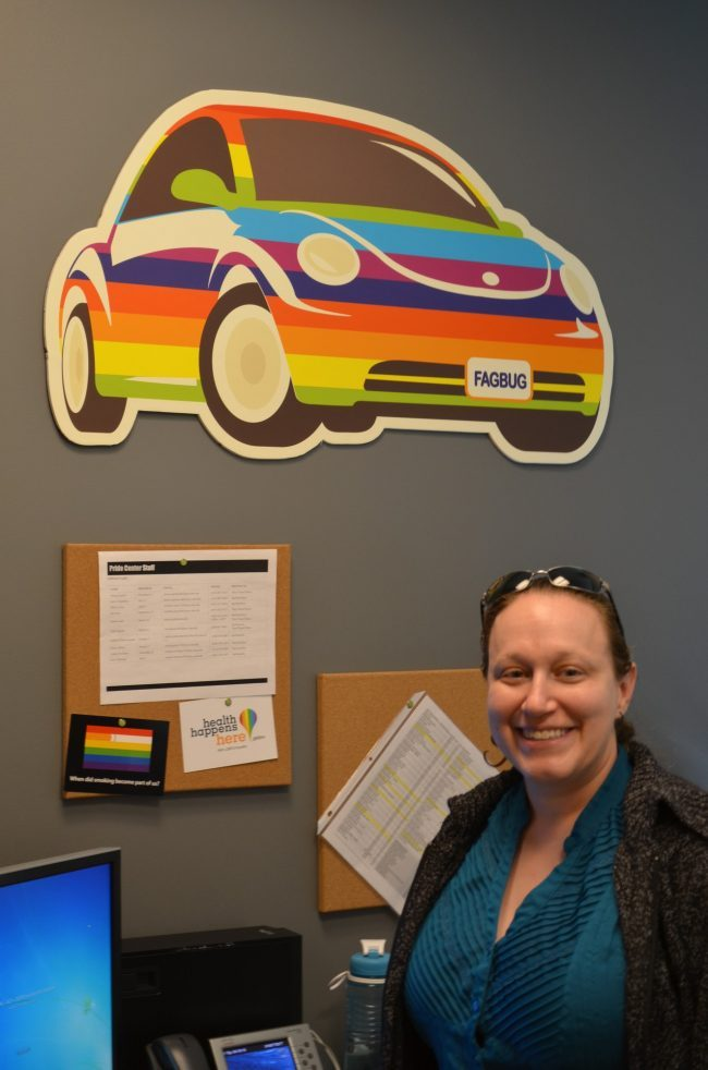 woman posing in office with rainbow colored car
