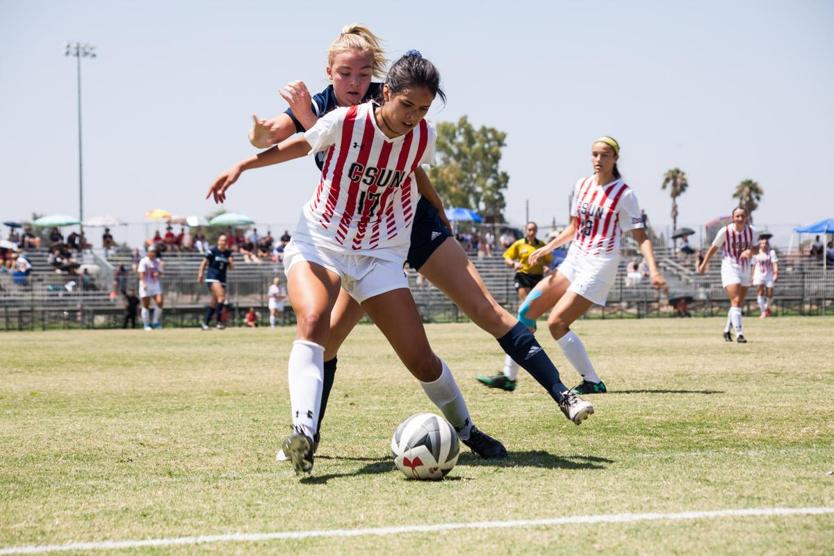 Amanda Martin shields the ball against a Northern Arizona attacker. Photo credit: Hanna Von Matern