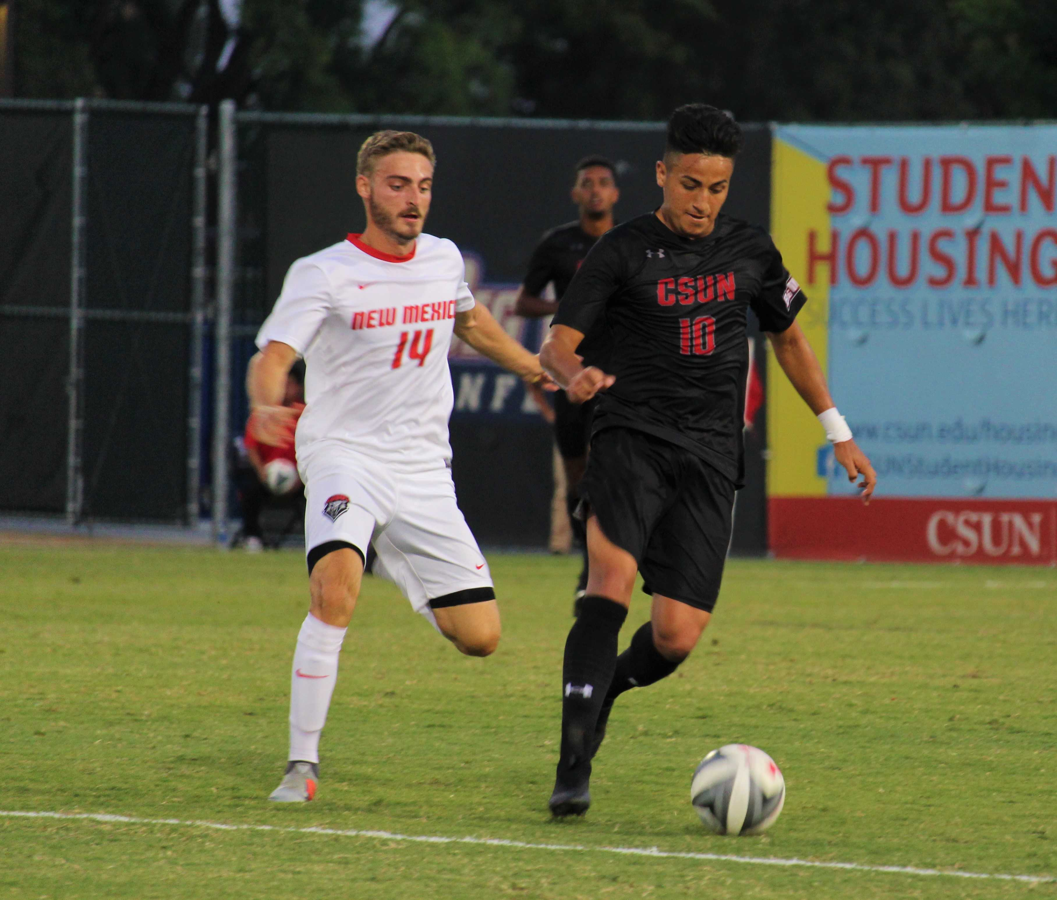 Forward Michael Flores dribbles away from a Photo credit: Justin Lee