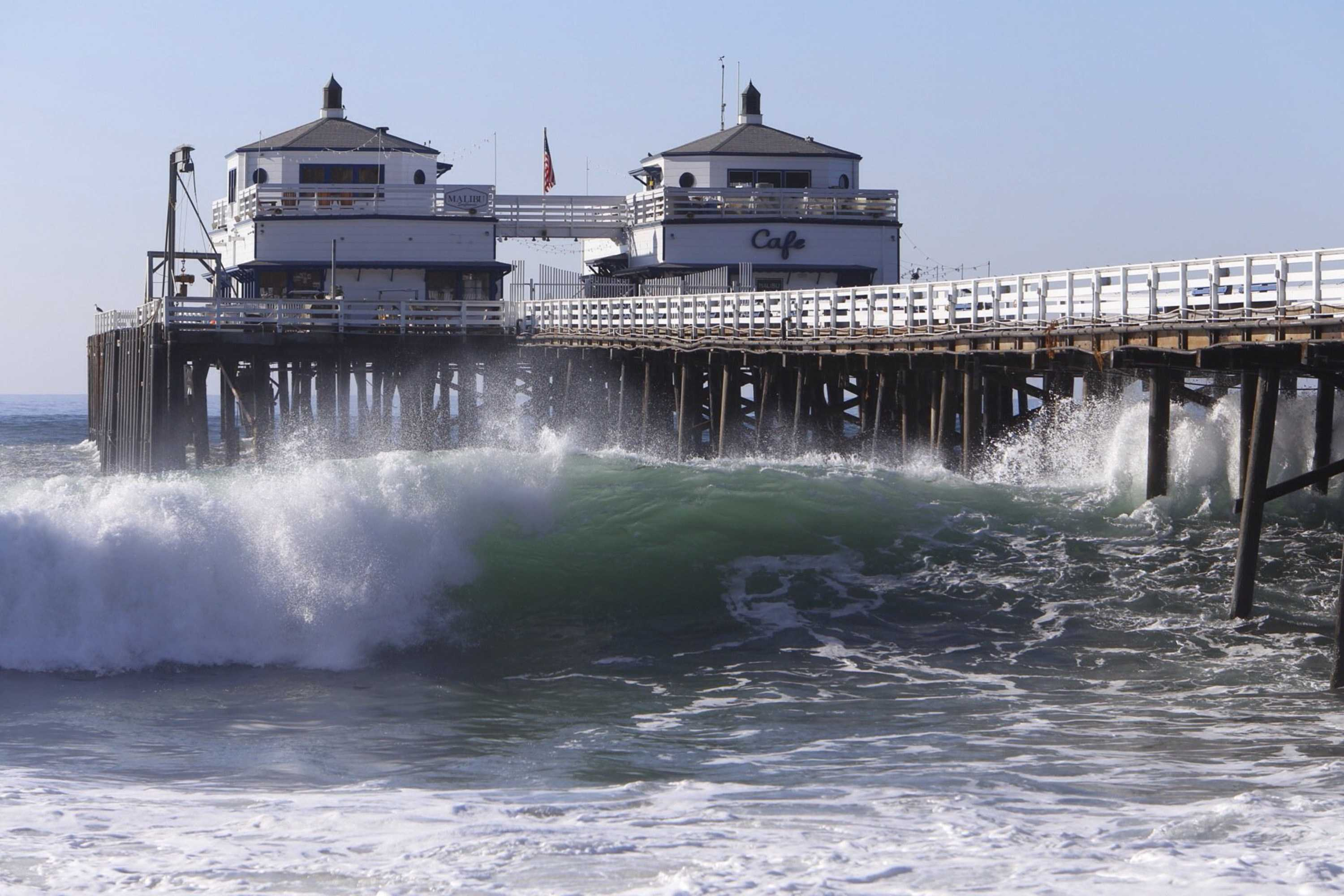 Huge swells generated by Hurricane Marie pound the Malibu Pier on Aug. 27, 2014, producing eye-popping waves for the bravest of surfers, while at the same time putting low-lying seaside communities at significant risk of flooding and beach erosion. A trio of new lawsuits are aimed at forcing the world's largest oil companies to pay for the projected effects of rising seas along California's coast. (Al Seib/Los Angeles Times/TNS)