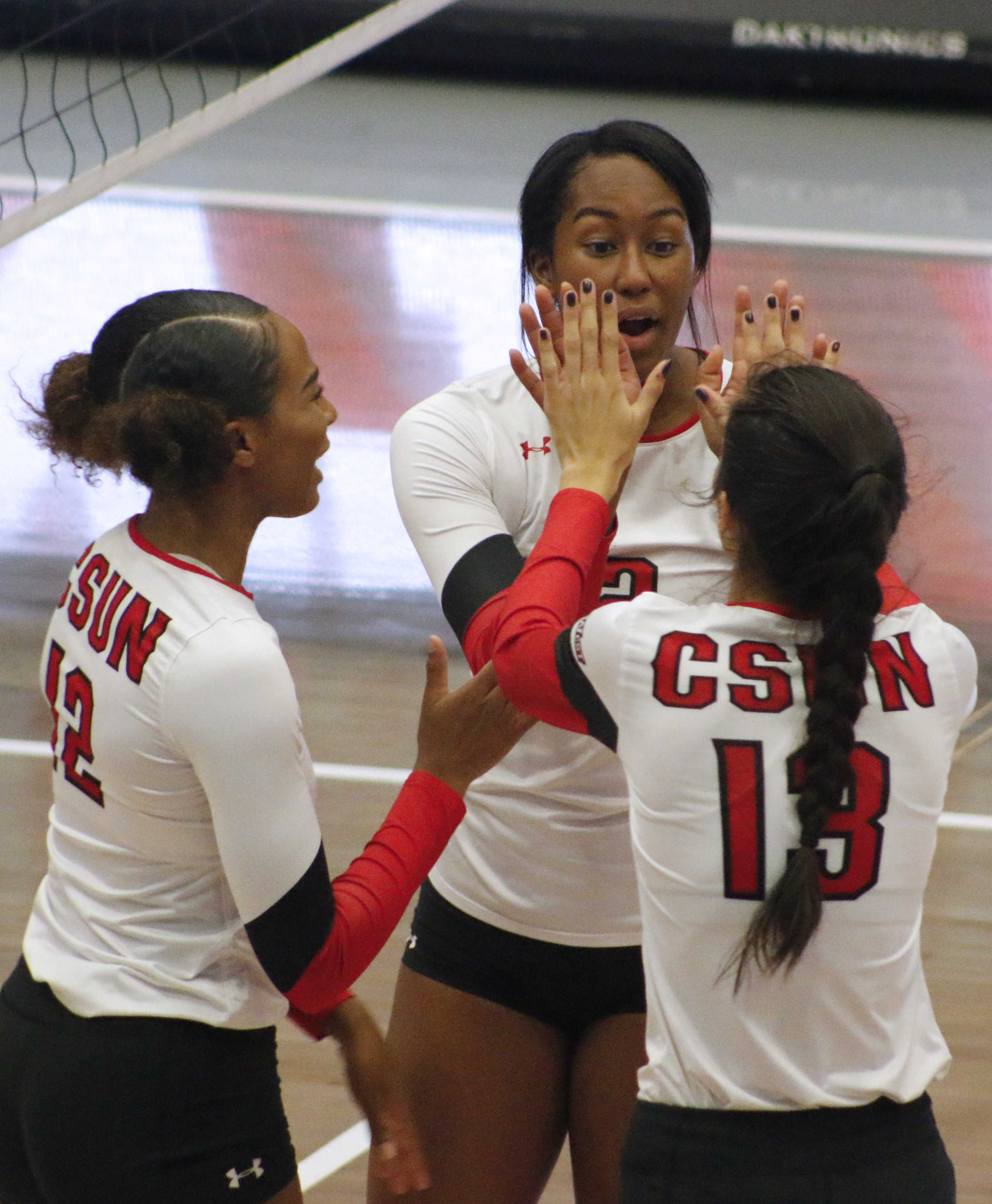 (Left to right) Brianna Johnson, Aeryn Owens and Nicole Nevarez celebrate after a point. Photo credit: Clare Calzada