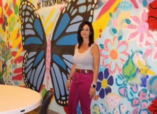 posing in front of mural