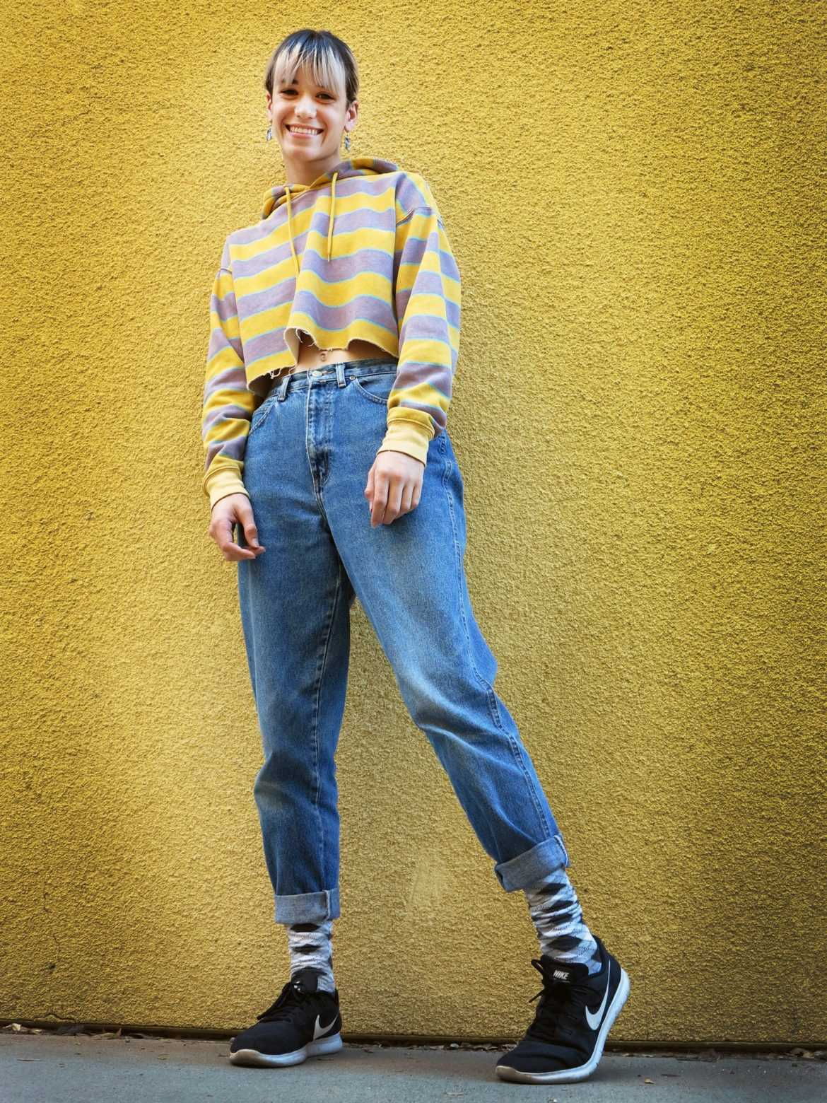 student dressing in front of yellow wall