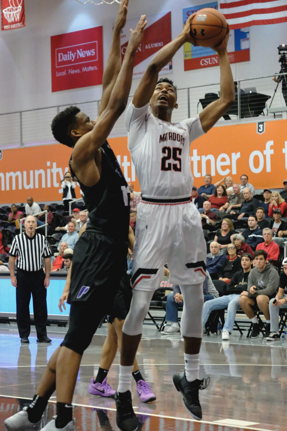 CSUN's Jared Pearre goes up for a bucket against a Portland defender. Photo credit: Jose Morales