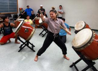 student hitting drum