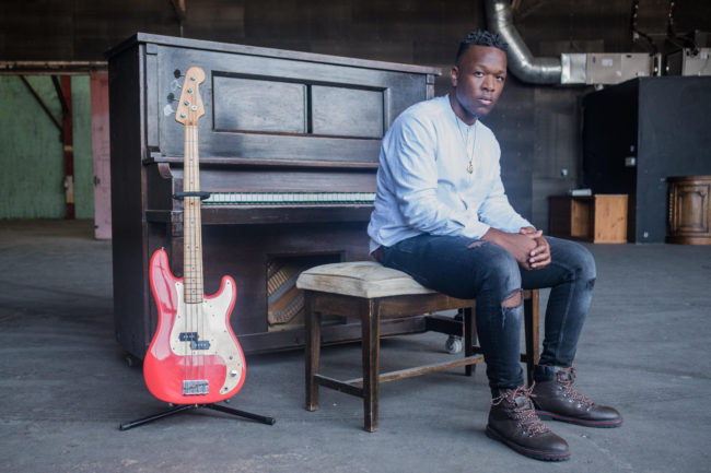 A male African American musician sitting on a chair in front of a piano and red electtrical guitar by the side.