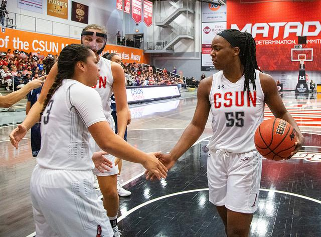 three CSUN women's basketball players in white jerseys giving high-fives to each other.
