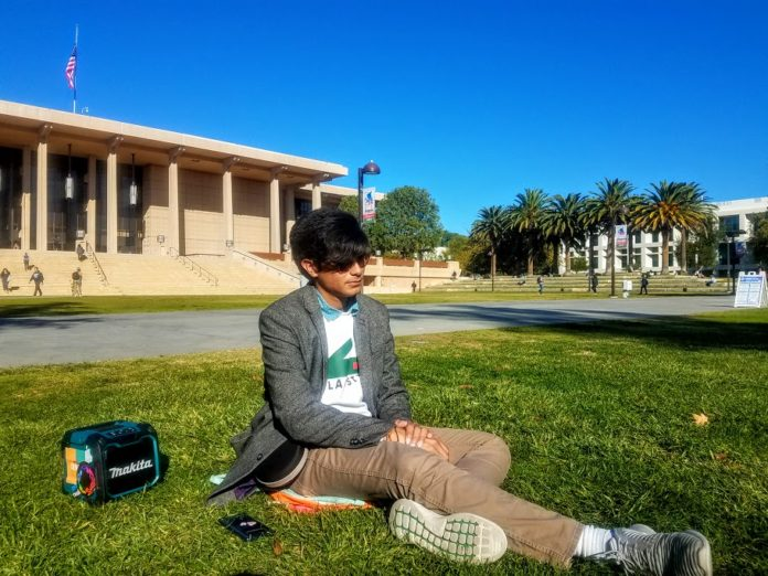 A male student sitting on the oviatt lawn enjoying the sunshine and having a colorful bluetooth speaker on the side.