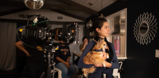 An actress filming with a dog in her arm.