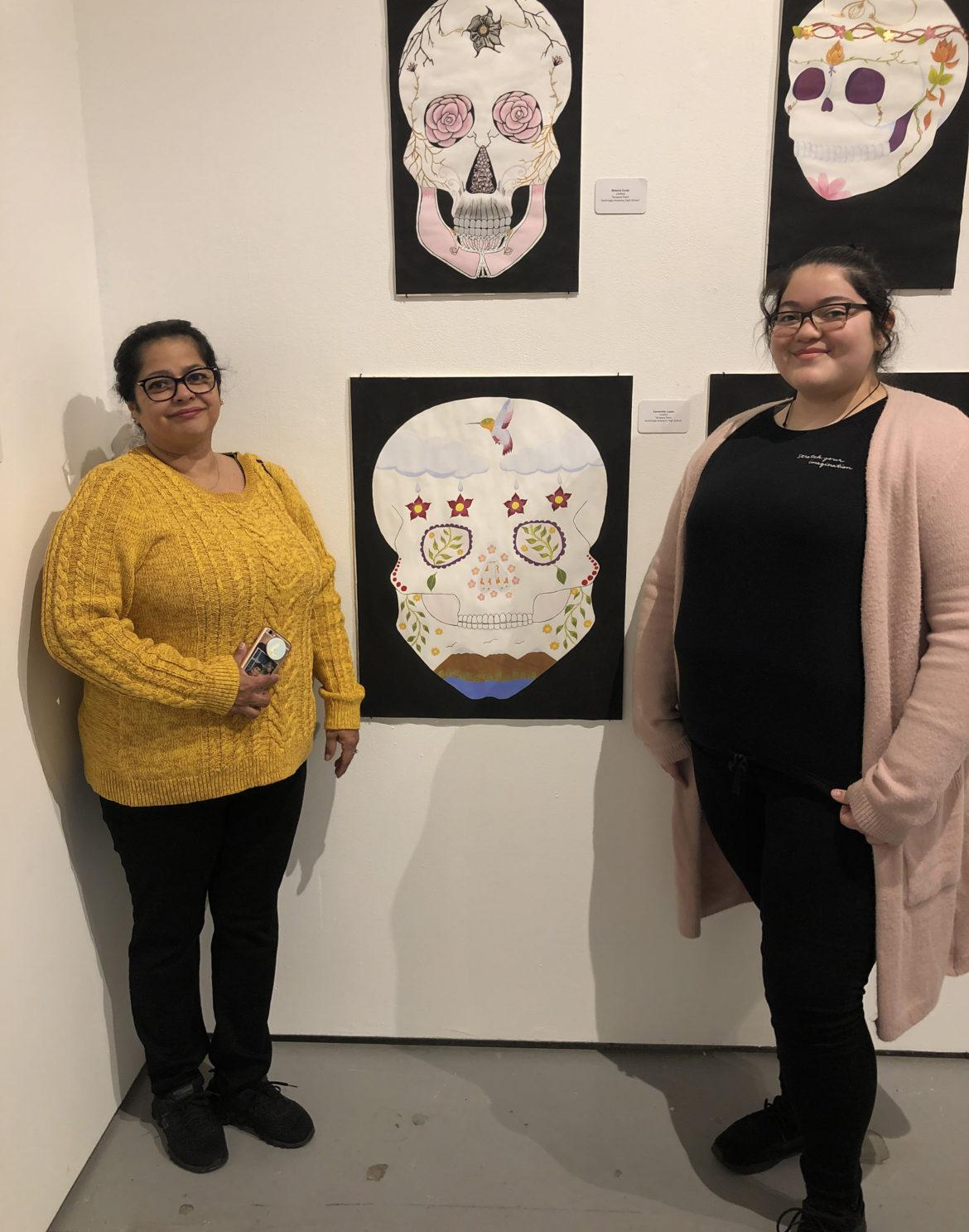 Two ladies taking picuture with a skull drawing
