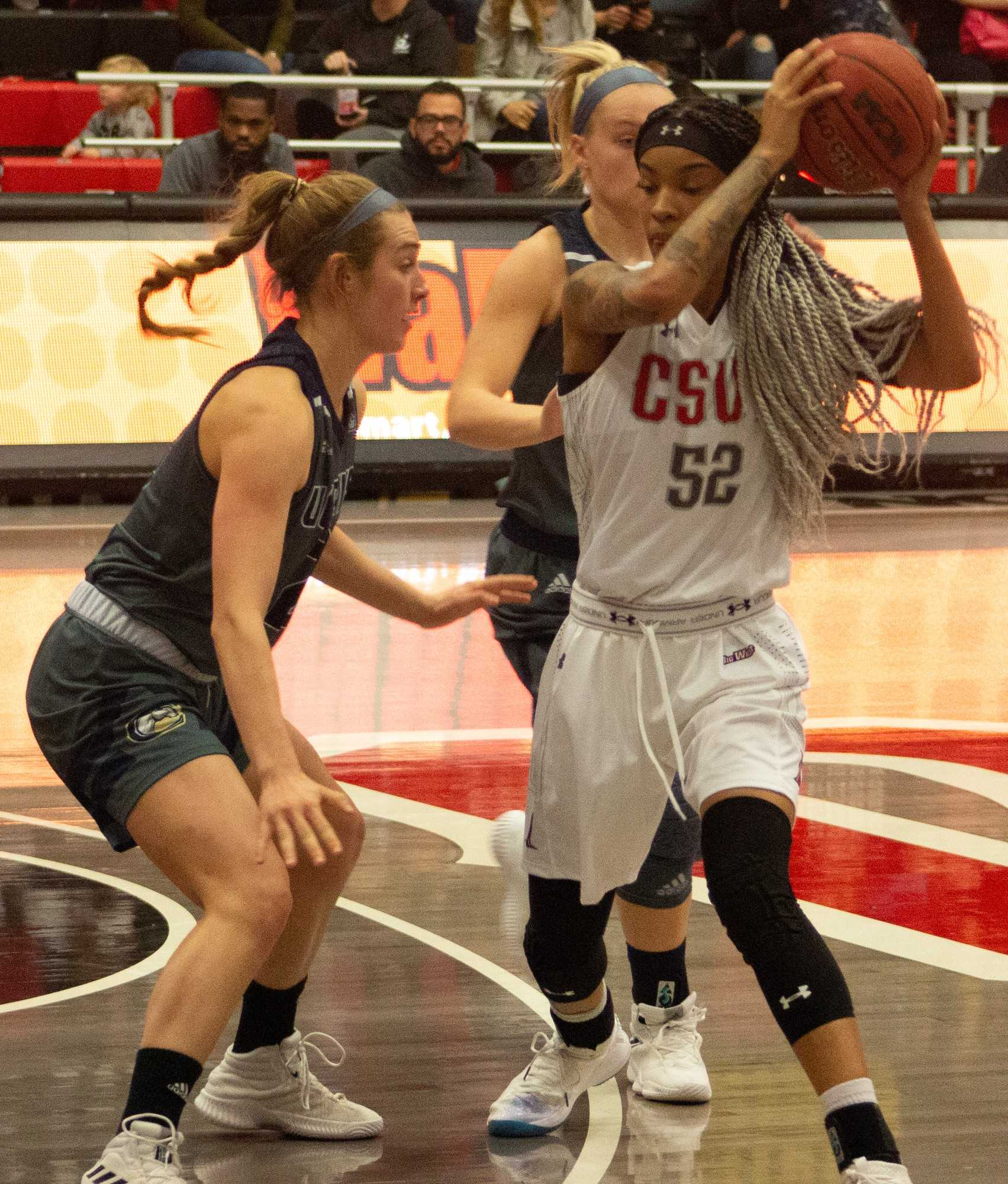 A CSUN Women's basketball player benig guarded by two players