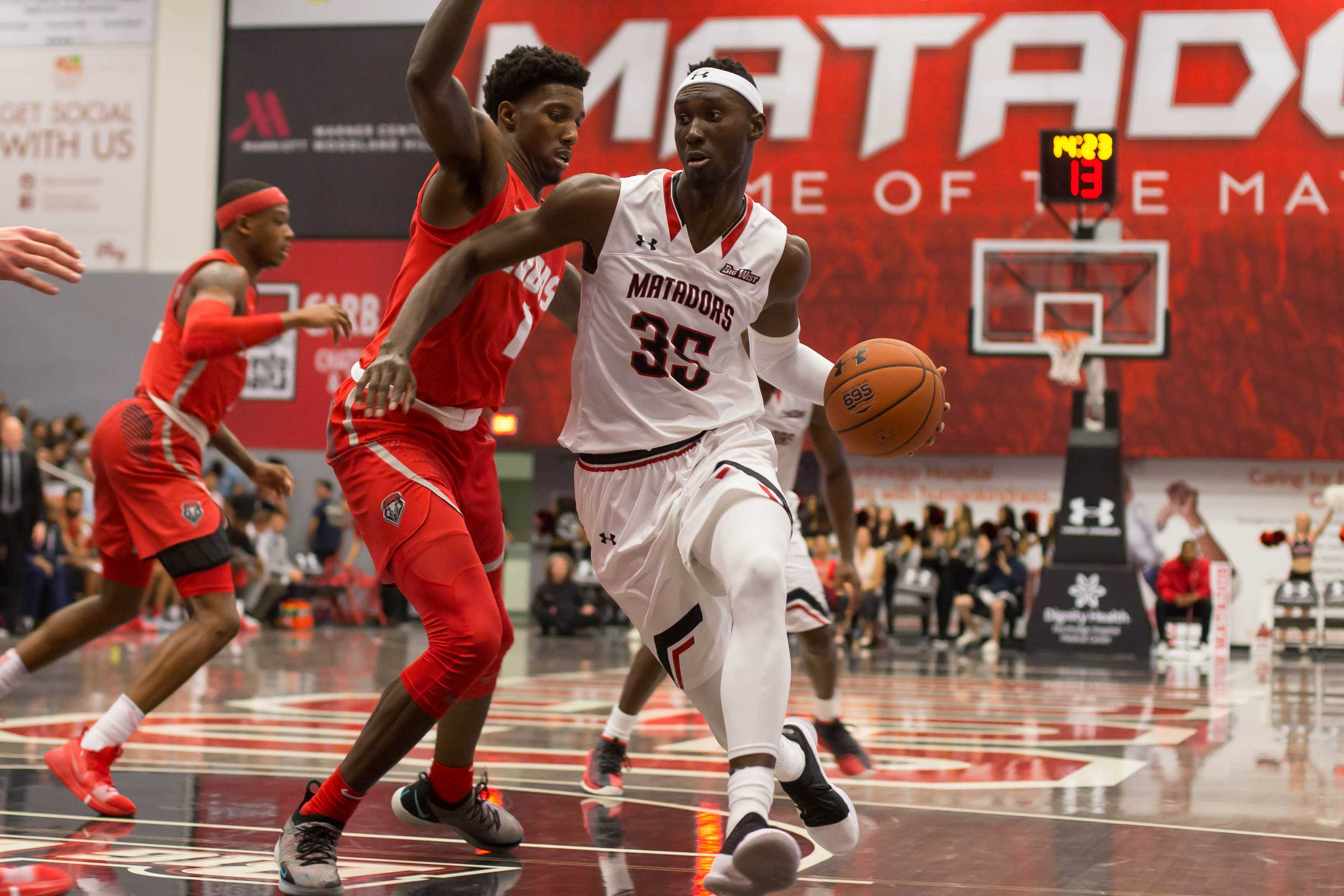 A CSUN Men's basketball player trying to get passed over the defender and score